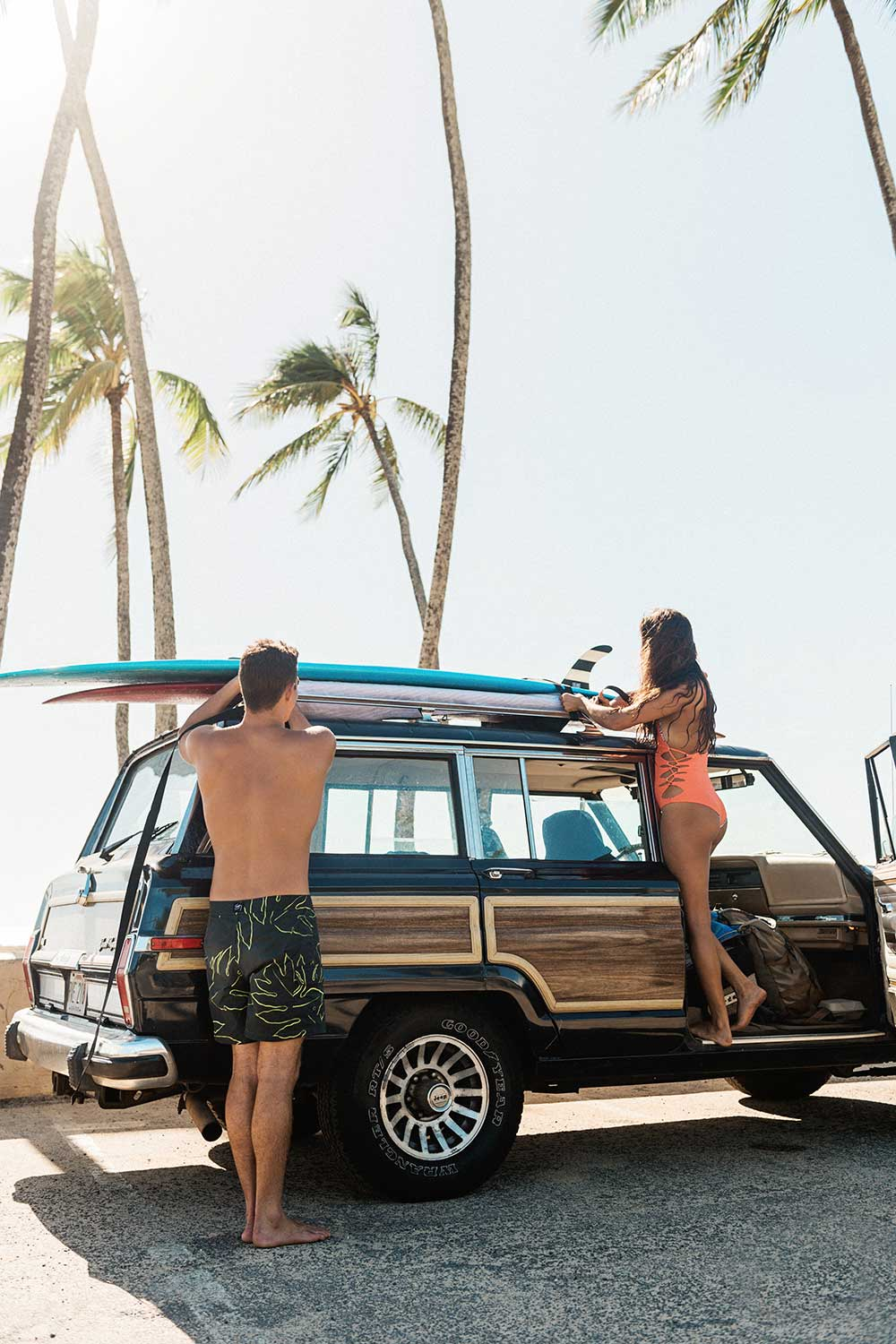 Man and woman taking surfboards from top of car