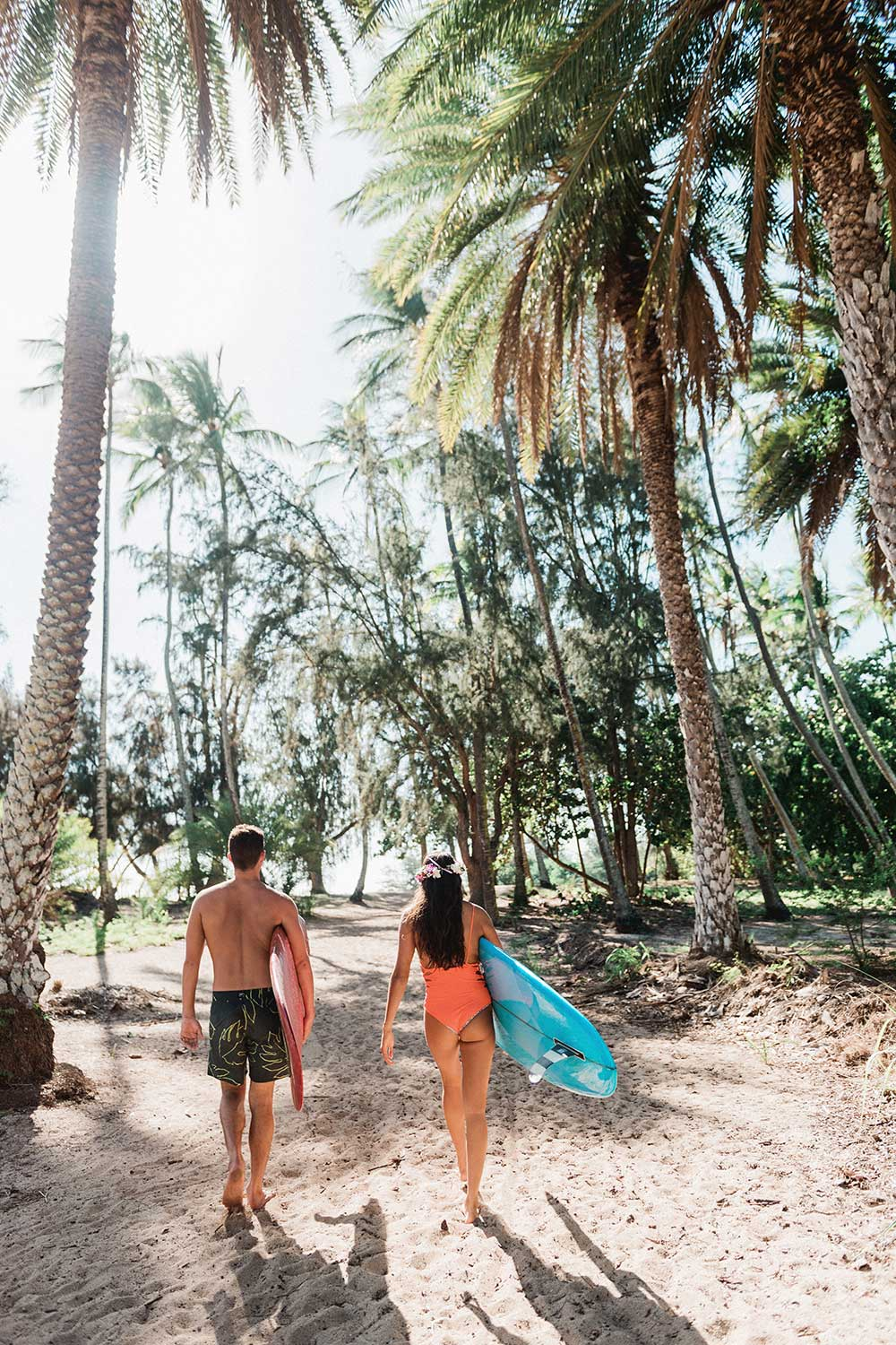 Man and woman in swimsuits walking to beach