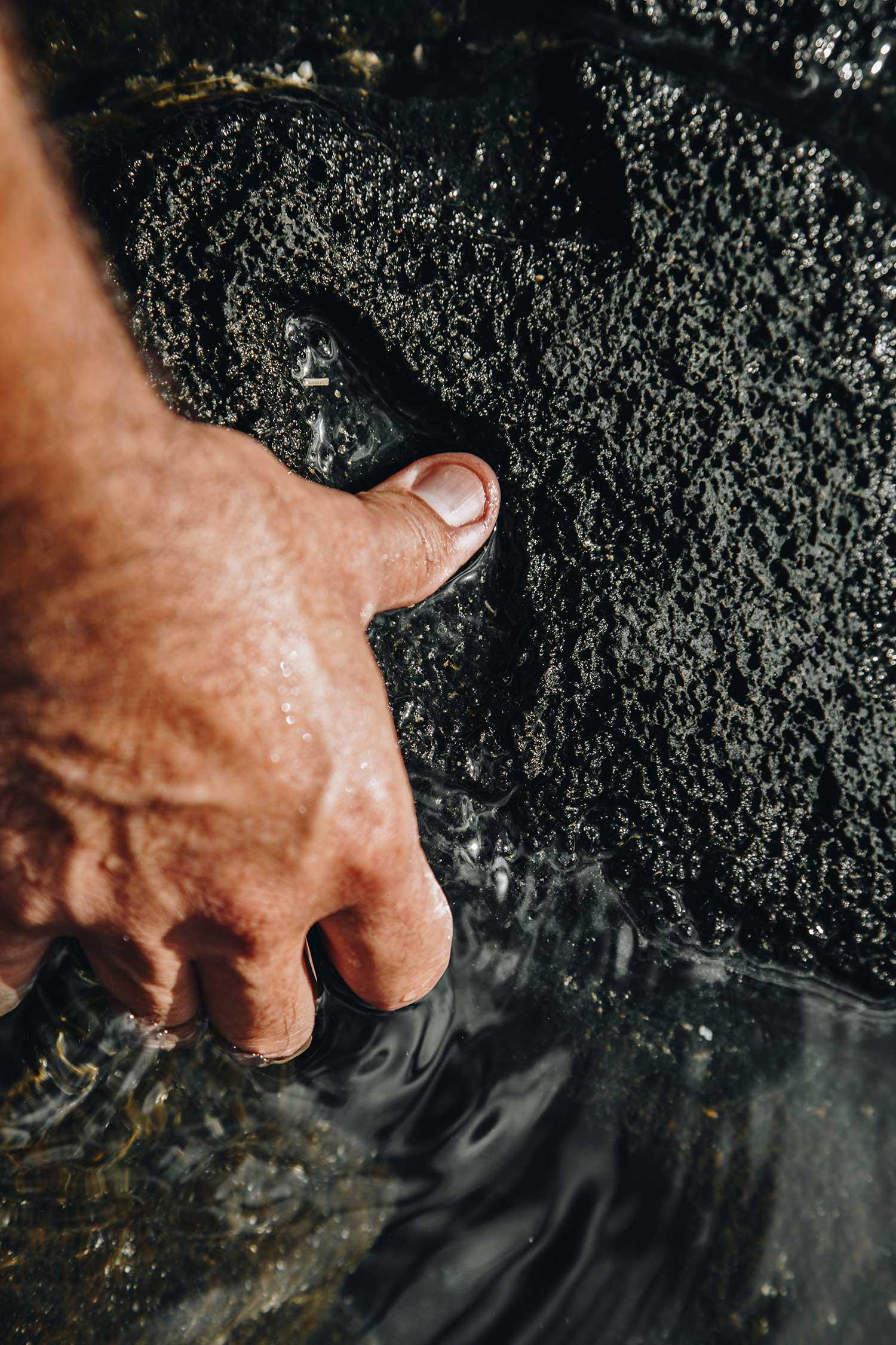 Hand in ocean against the rocks