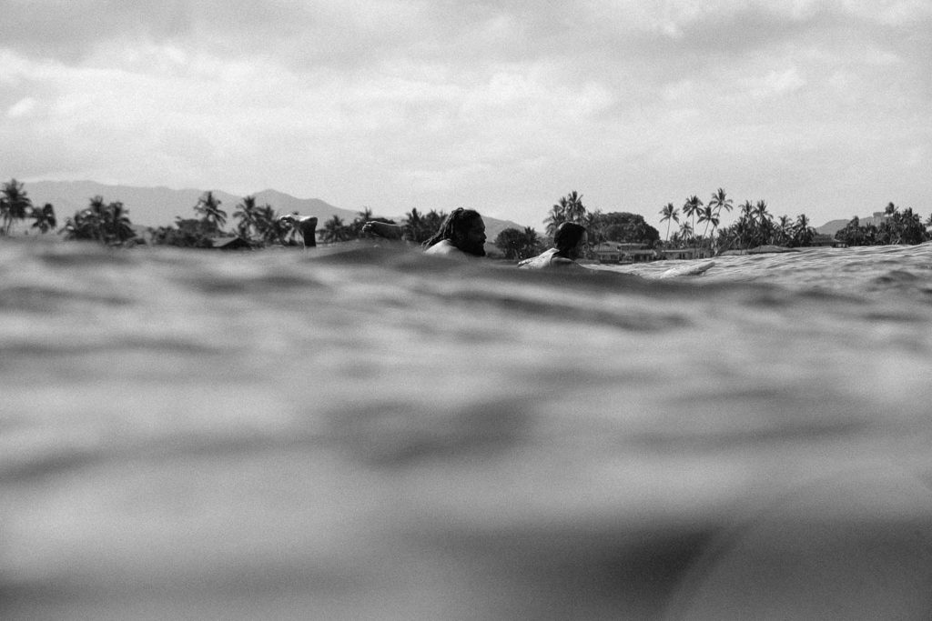 Black and white photo of tandem surfers paddling out to surf