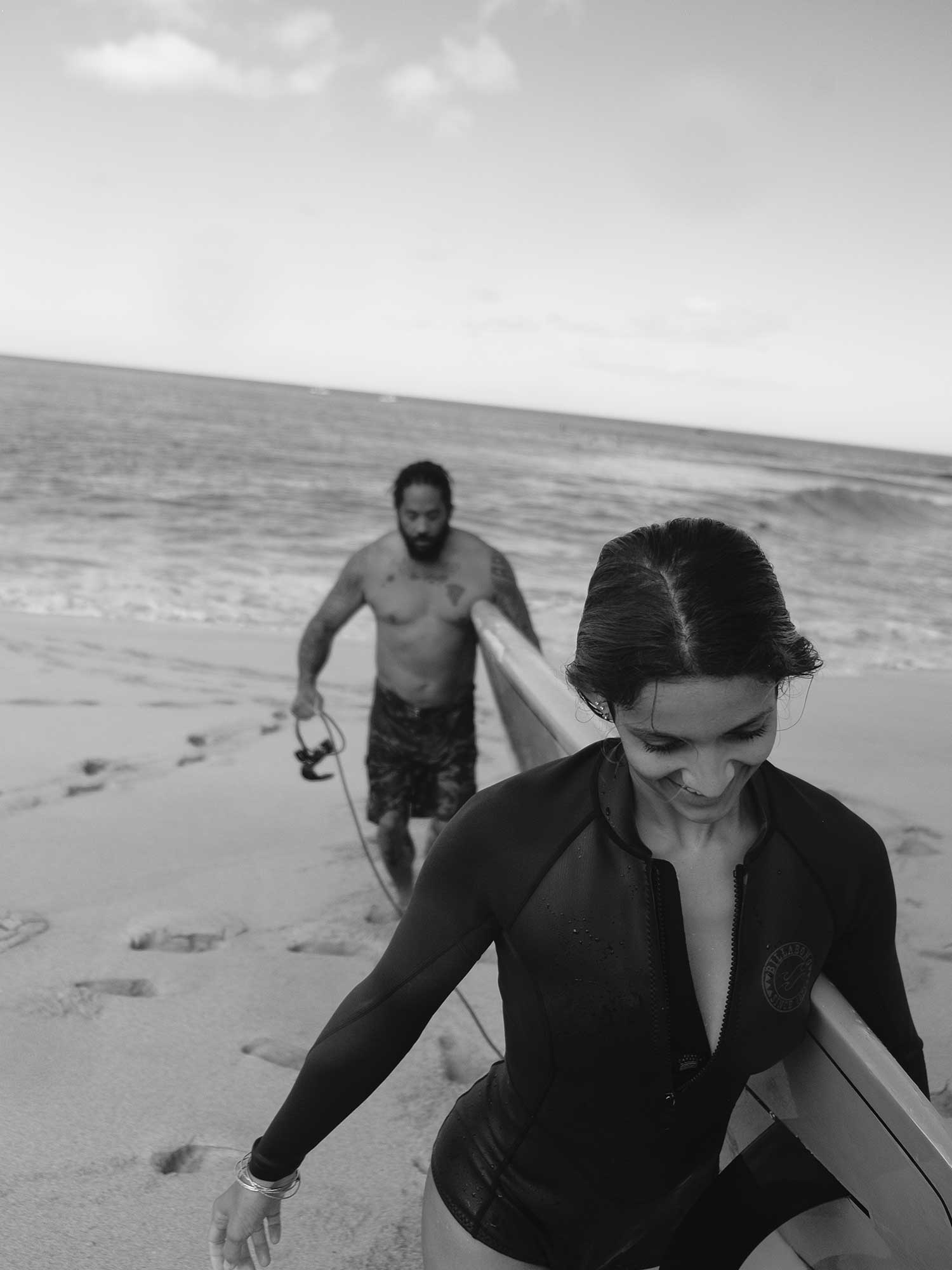 Jordan and Keala walking back to shore with their surfboard