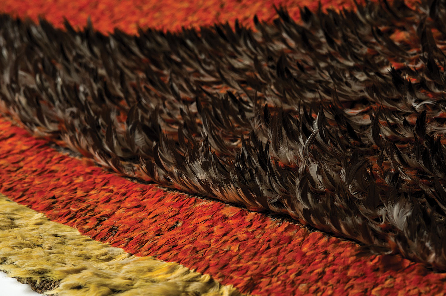 Red-orange, brown, and yellow featherwork