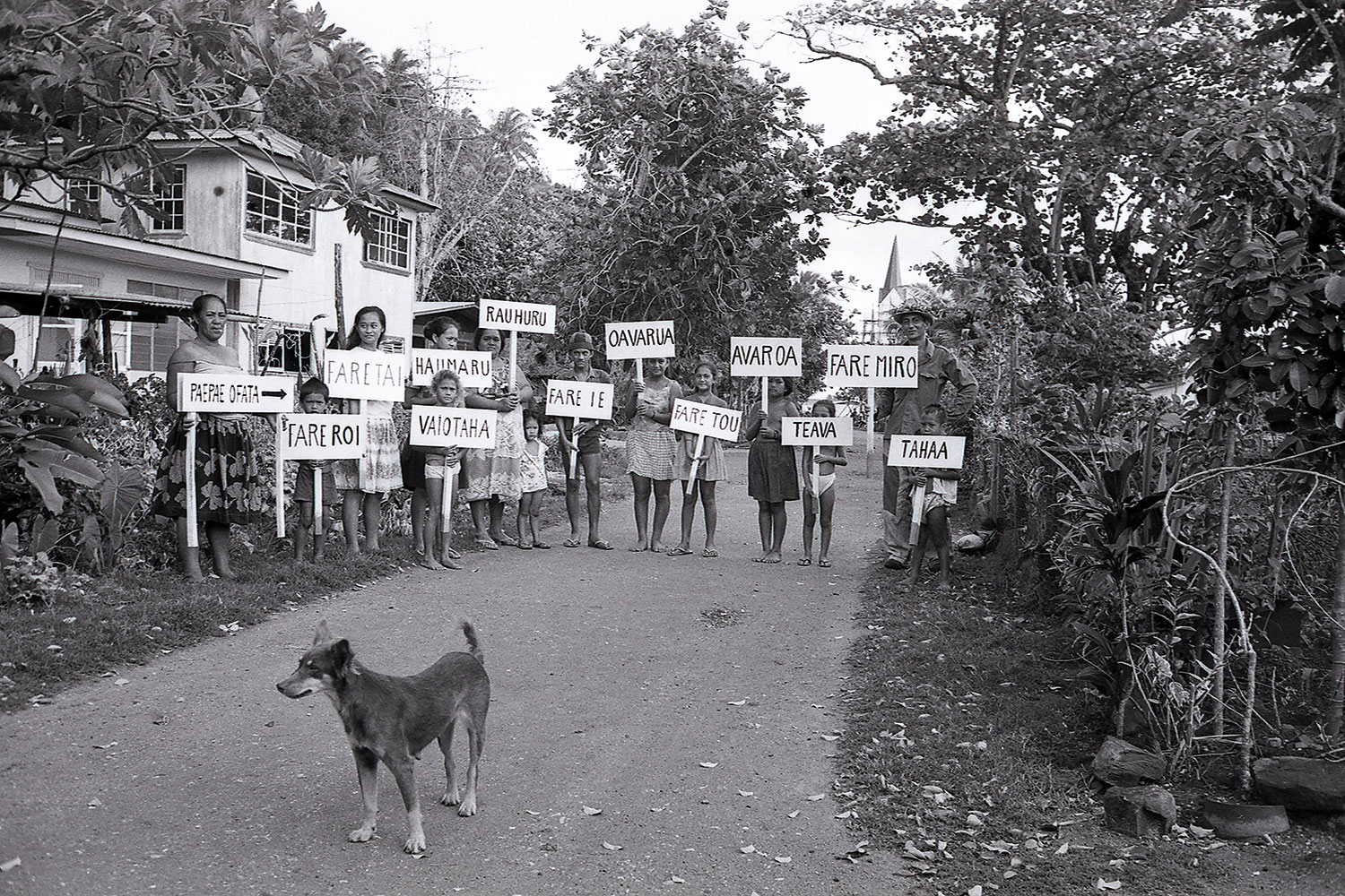 Black and white photo of various aged people holding signs, with a dog in the foreground.