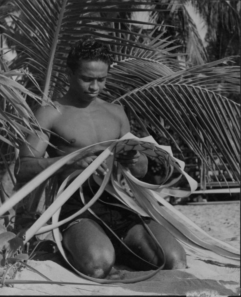 Black and white developed image of man weaving with coconut leaves.