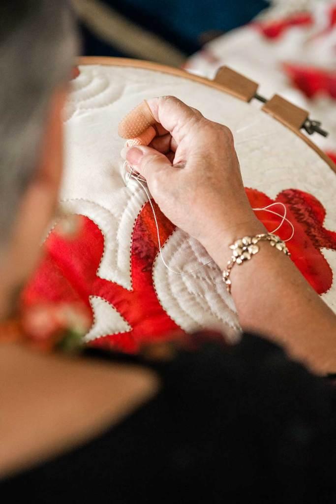 Patricia Lei Murray threading through her quilt.