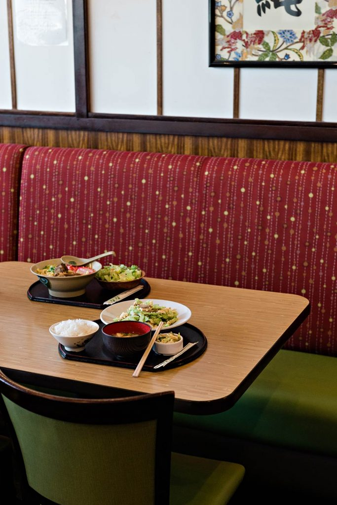 Two trays filled with food—placed in a dining booth.