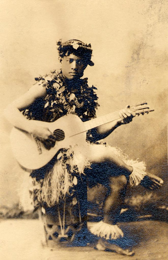 Photo of a young man dressed with various lei and holding a guitar.