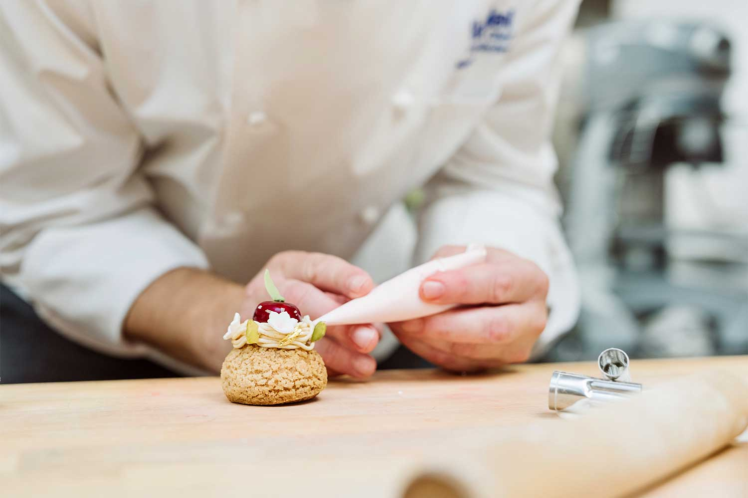 Close up shot of a pastry chef finishing icing on a small biscuit