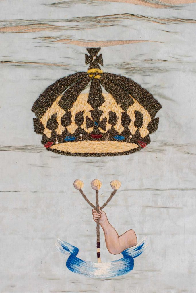 A crown suspended over an arm holding a three pronged staff above a small blue banner