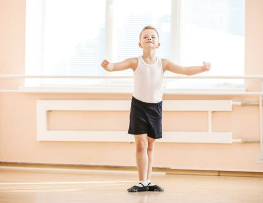 boy in ballet shoes in front of bar