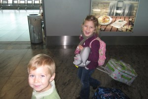 Oliver and Anna walking through the airport with carry-ons
