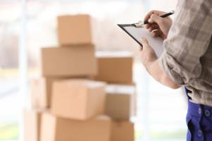 Man holding clipboard on blurred boxes background