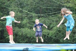 Oliver, Samuel, and Anna jumping on a trampoline