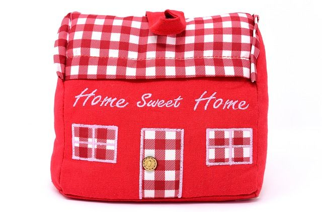 red house-shaped pillow with home sweet home written on it