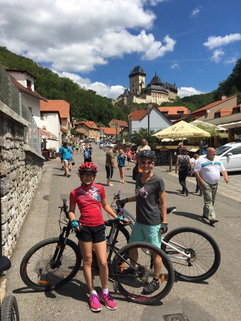 Emily and Anna on bikes below Karlstejn Castle