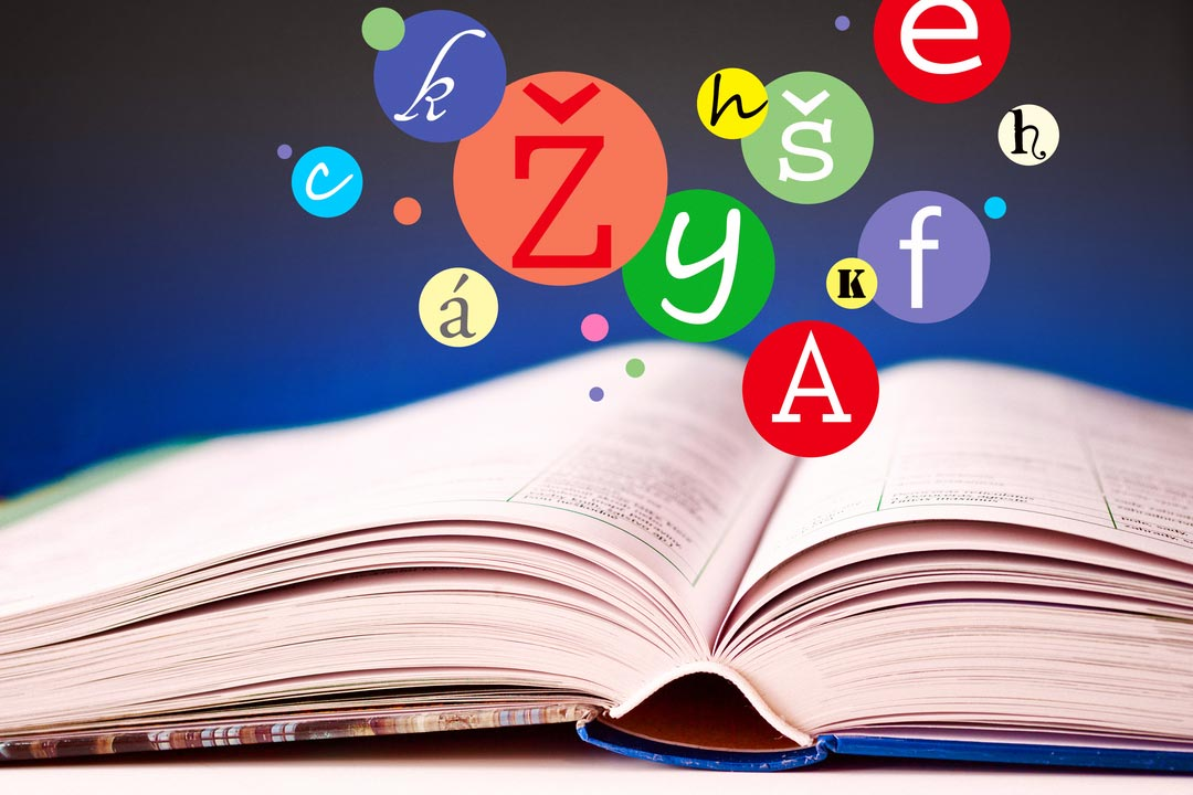 open book with pages - literature and education - czech language textbook and flying diactritics symbols - photo by kaprik/Shutterstock.com
