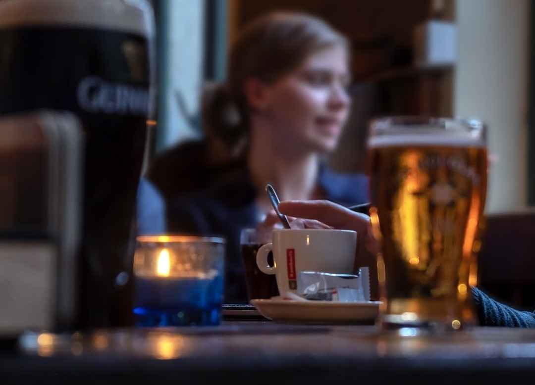 a table top with a beer and coffee and a woman in the background