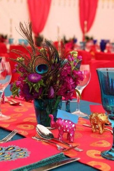 East Indian Boho centerpiece - peacock feathers, elephants, and bright colors. Small World gets big with cultural party themes | Halfpint Design