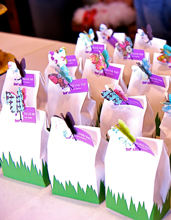 Butterfly First Birthday Party | Halfpint Design - Party favor bags filled with caramel popcorn. Decorated with grass and butterflies that hold the thank you note.