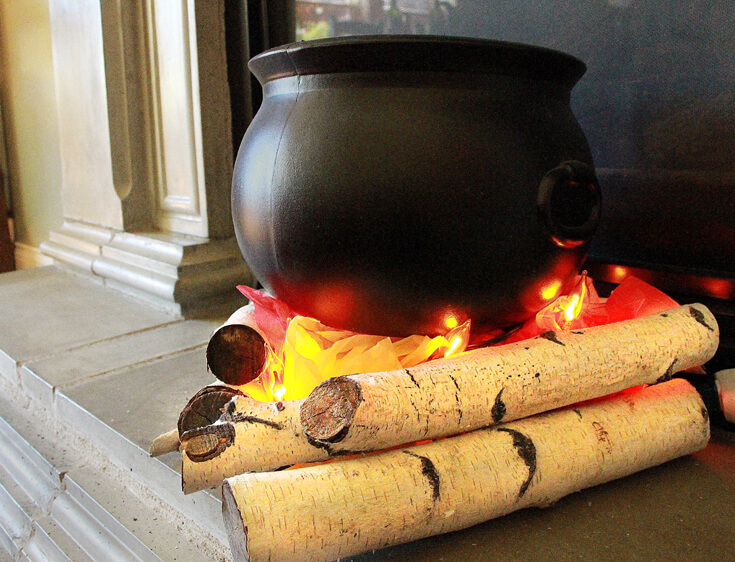 Step 5: Balance the cauldron so it is slightly inside the triangle. Create an Eerie Witches' Cauldron   Halfpint Design - Halloween decorations, witch decor, faux fire, fake campfire, firelight bulbs
