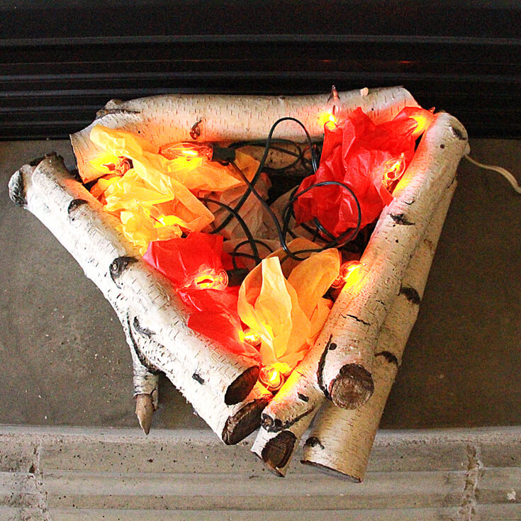 Step 4: Place the flickering fire bulb string in the middle and arrange bulbs to stick out around the edges while concealing the cord with the tissue paper. Create an Eerie Witches' Cauldron | Halfpint Design - Halloween decorations, witch decor, faux fire, fake campfire, firelight bulbs