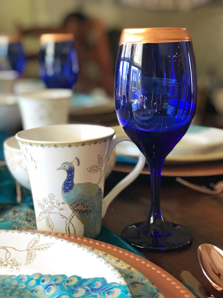 Peacock China and DIY copper rimmed wineglasses with Far East flair makes for exotic Thanksgiving, Christmas, or dinner party table decor. See more Global Chic Holiday Tablescape ideas at Halfpint Design. Thanksgiving Tablescape, Place setting, Christmas Table, Holiday decor.