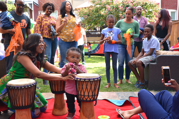 Baby playing with a shaker on a bongo for a ONE LOVE first birthday party.