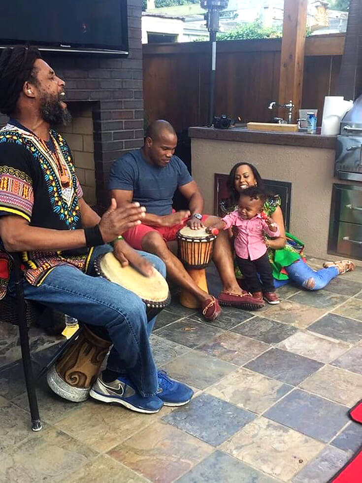 Men playing drums while mom and baby watch for a ONE LOVE first birthday party
