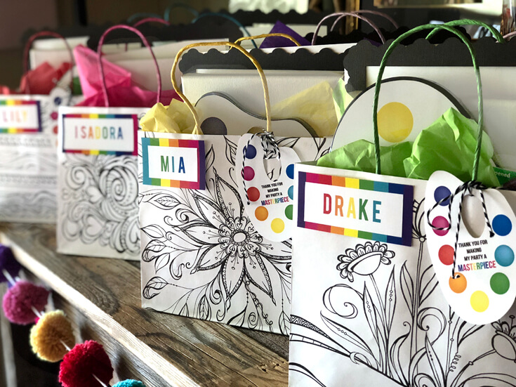 Black and white floral bags with rainbow name tags and a personalized paint palette tag as Art Party Favors