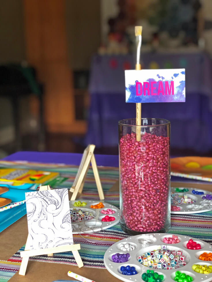 Glass vase filled with pink popcorn kernels, mini easel, and paint palette filled with rainbow colored beads for an Art Party