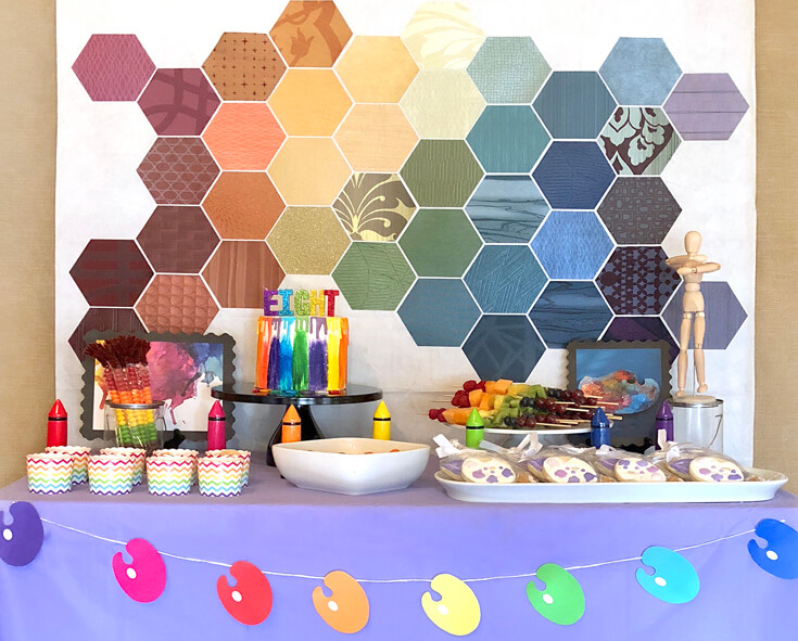 A colorful food table for an Art themed birthday party. Purple table cover, rainbow paint palette banner, and rainbow hexagon backdrop.