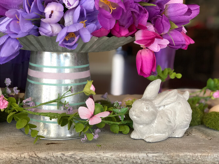 Ceramic bunny next to galvanized vase with a large bunch of purple tulips.