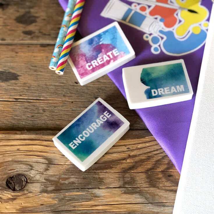 Watercolor printed erasers with inspirational words on wood counter with rainbow pencils and purple paint smock. Party favor ideas for an Art birthday party.