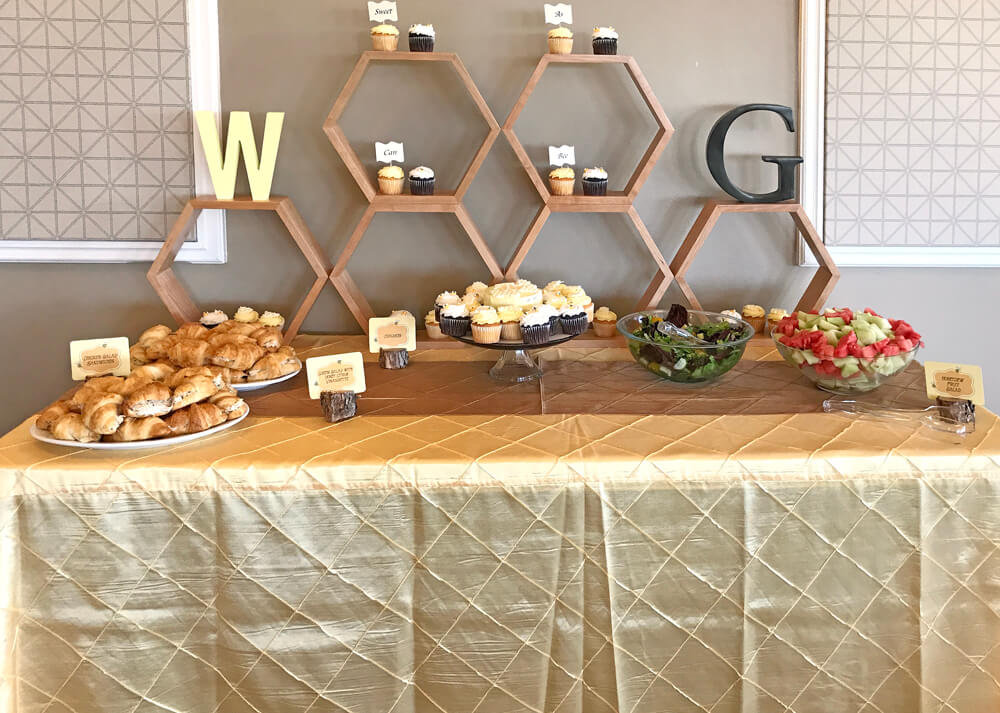 Honeycomb shelving used o display cupcakes on food table at Mommy to Bee baby shower