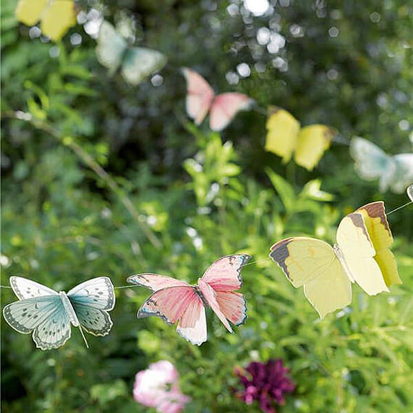 Paper butterflies on string to create a 3D effect bunting for an Enchanted Butterfly party.