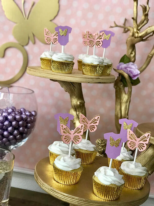 Butterfly toppers on vanilla cupcakes on gold stand for an Enchanted Butterfly party.