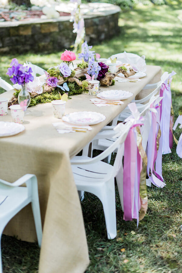 A gorgeous table setting of moss, wood, flowers, ribbons, and butterflies for an enchanted butterfly party.