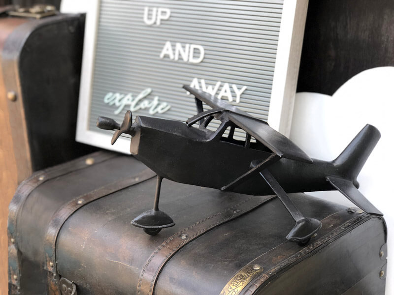 Up up and away message on letter board with metal airplane on vintage suitcase for Little Explorer baby shower