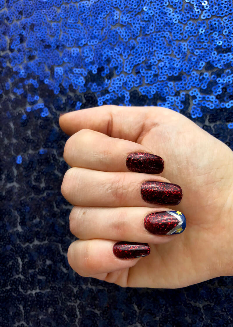Hand with painted red glitter nails and wonder woman accent for Wonder Woman party.