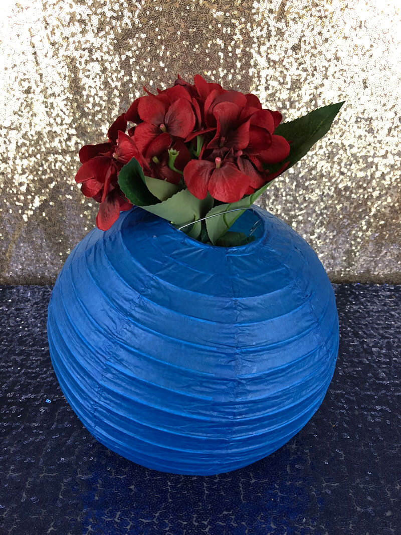 Adding flowers to the blue paper lantern for a Wonder Woman themed floral lantern centerpiece tutorial.