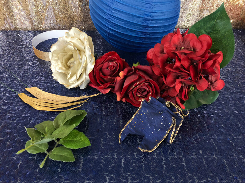 A collection of red and gold flowers and blue ribbon for a floral lantern centerpiece.