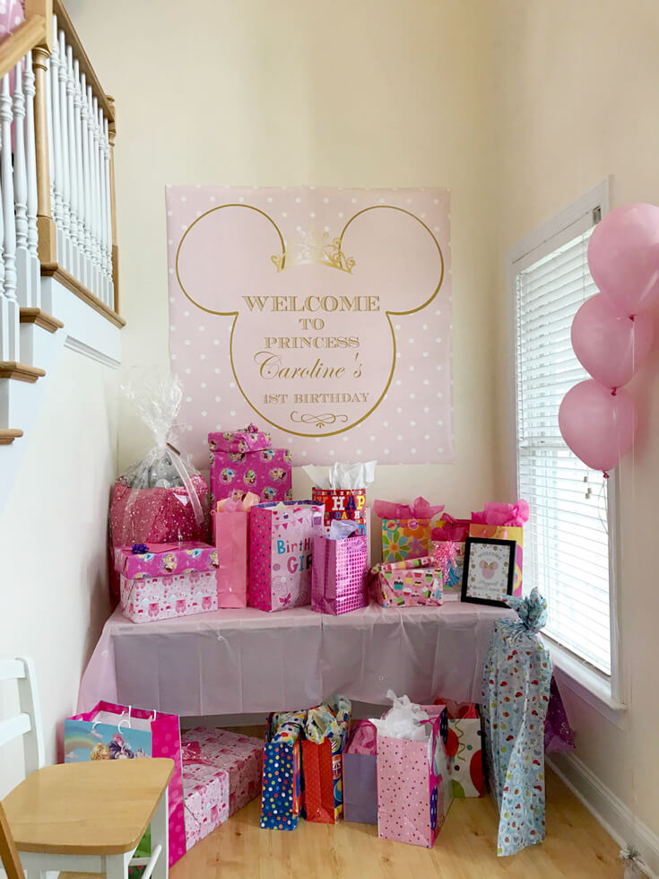Gift table with large welcome banner for Minnie Mouse first birthday party