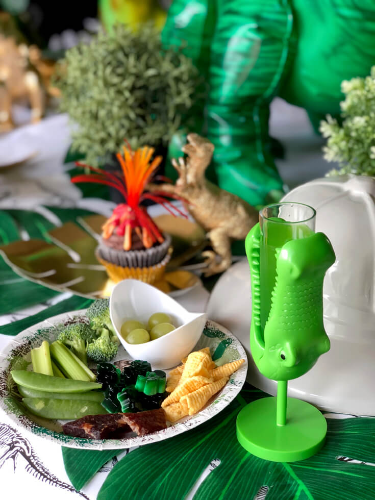 Plate loaded up with party food, reptile cup with green punch and volcano cupcake for a dinosaur birthday party
