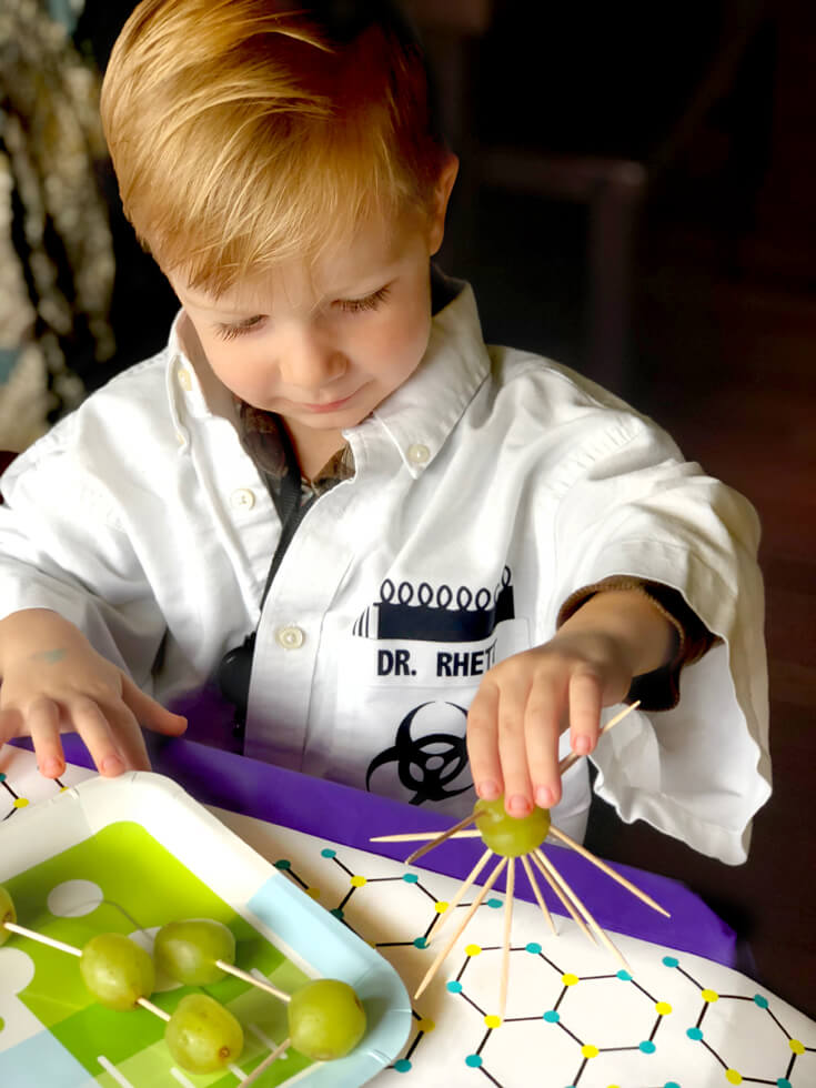 Boy making a grape and toothpick creature during mad science party activity
