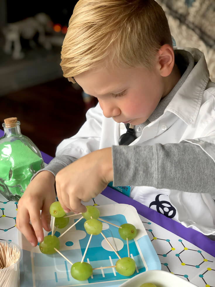 Boy making a grape molecule for a food science activity