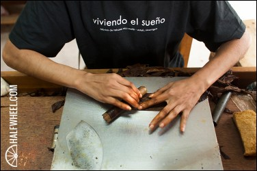 "A worker rolls a RoMa Craft cigar while wearing a shirt with the saying ""viviendo el sueño,"" which translates to ""living the dream."""