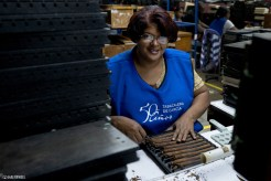 This woman is checking cigars in molds, she is also smiling.