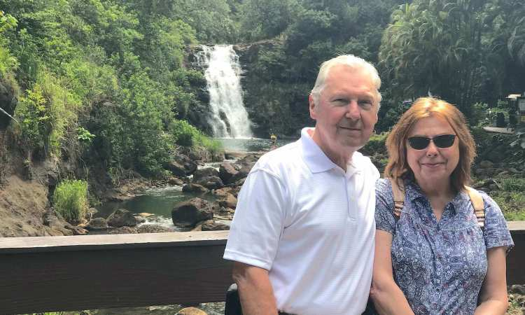 Couple in Waimea Valley in front of North Shore waterfall