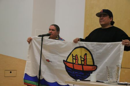 Ron Tremblay, former councillor for Tobique First Nation and member of Wolustuk Grand Council and Clayton Thomas Muller of Mathais Colomb Cree Nation in Treaty Six (Northern Manitoba), display the Wolustuk Grand Council flag. [photo: M. Howe]