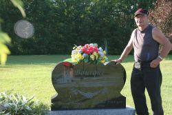 Paul Bourque stands beside his brother's tombstone. [Photo: M. Howe]